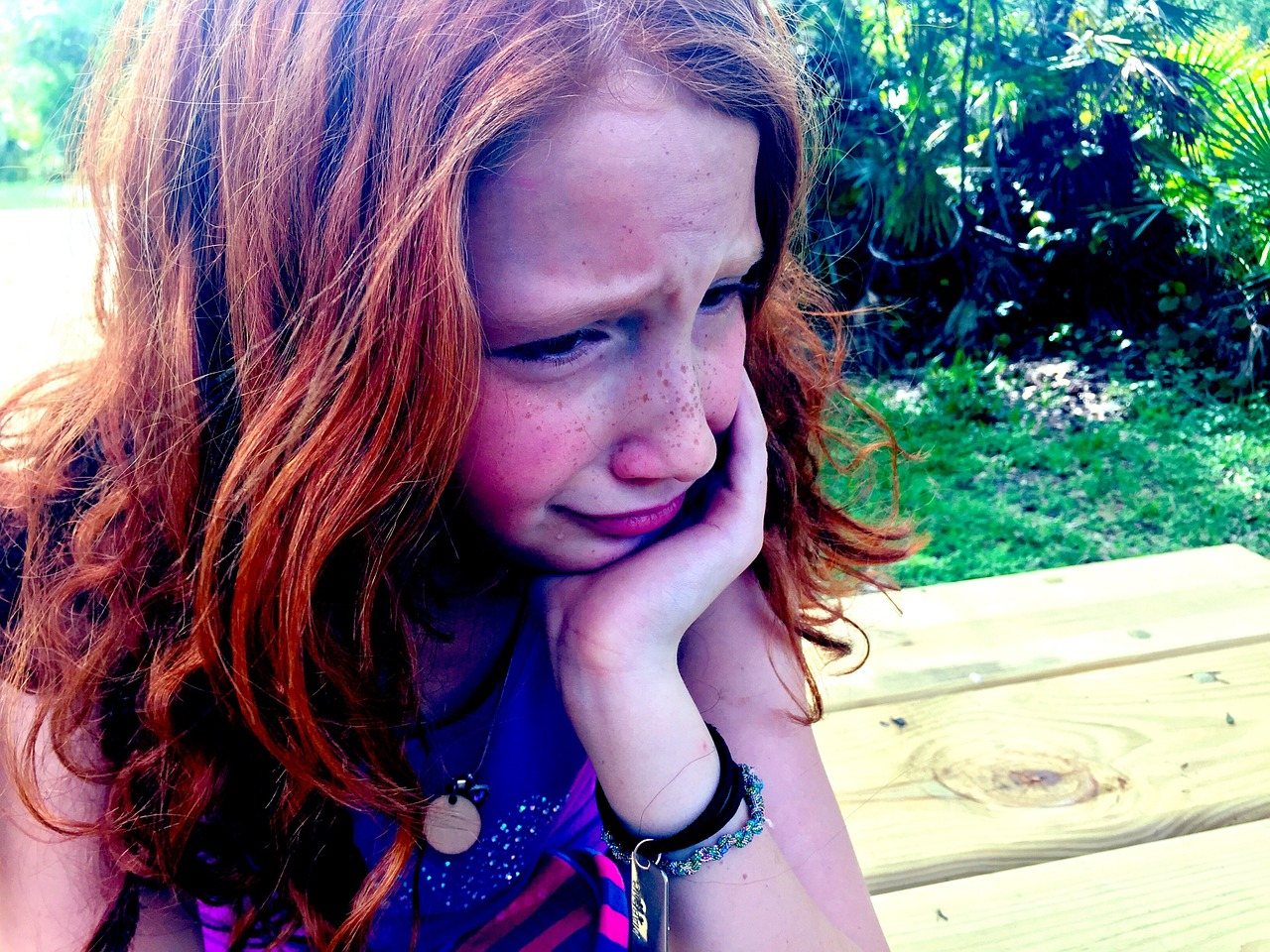 Close up of a young girl with long red hair looking upset